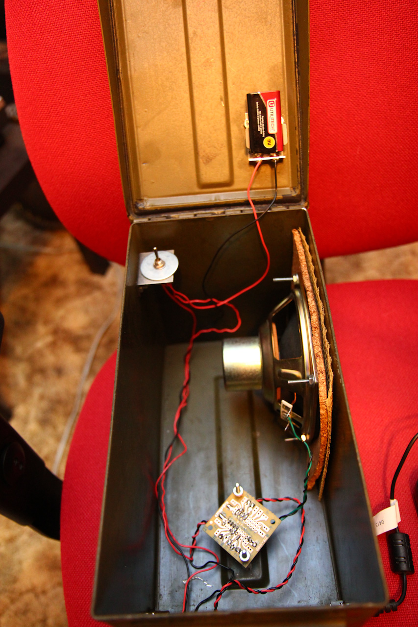 Scott's circuit, mounted inside his enclosure, a .50 cal ammunition can. Note his battery holder on the underside of the lid, power toggle switch, and the primary audio circuit mounted to the raised indentation on the enclosure's base.
