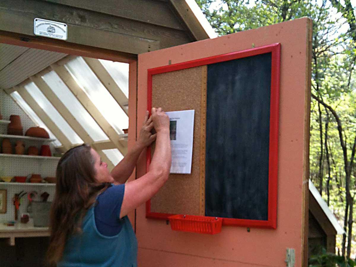 Bulletin board/chalkboard in use on Carole's potting shed door.