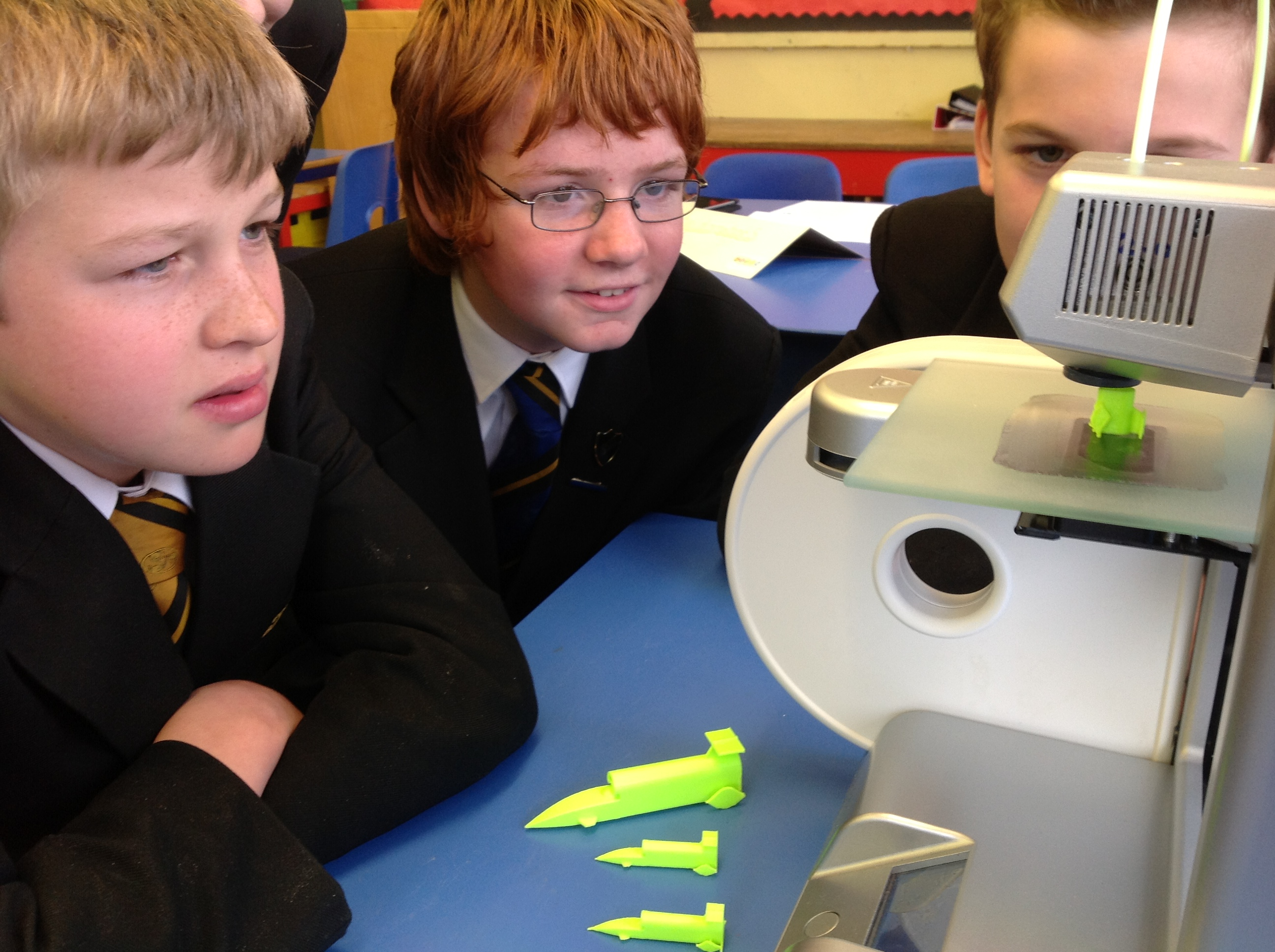 School children watch the Cube 3D printer at work.