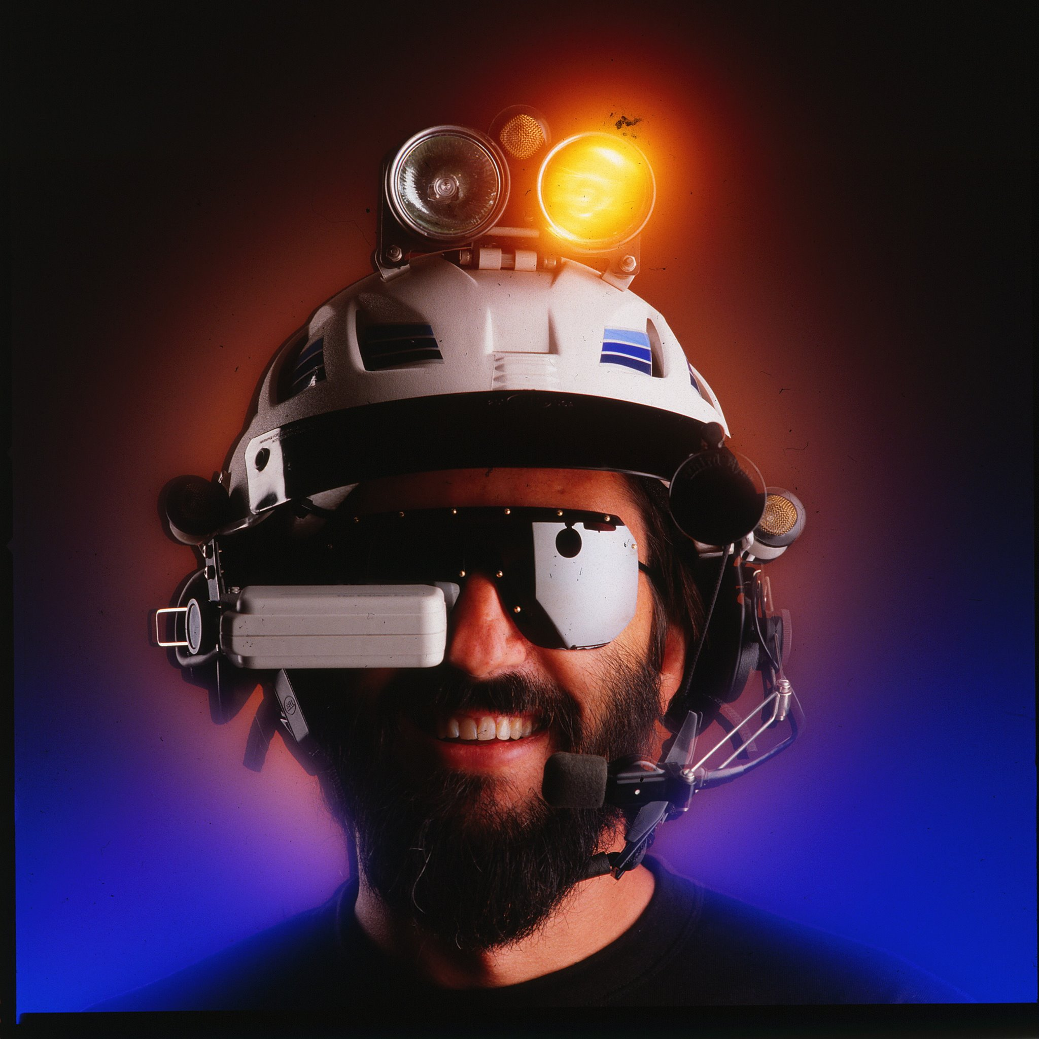 """Steve Roberts and the """"Brain Interface Unit"""" for his nomadic """"BEHEMOTH"""" bike project. The BIU offered a heads-up data display (via The Private Eye), a head-gesture-controlled mouse, radio communications and entertainment audio, spot and flood lights, a rear view mirror, and even a helmet liquid cooling system."""