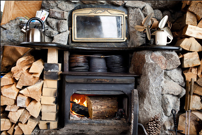 The cabin is heated by wood stove only. There's a makeshift oven at top, as well as copper coils that are used to heat water.