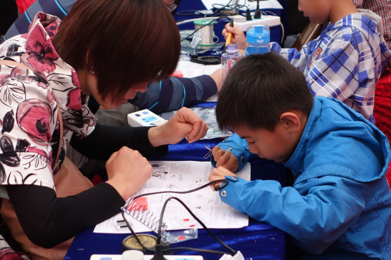 An intent young boy works on soldering
