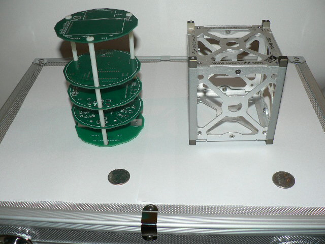 TubeSat and CubeSat, two variants of a picosatellite, with quarters shown for scale