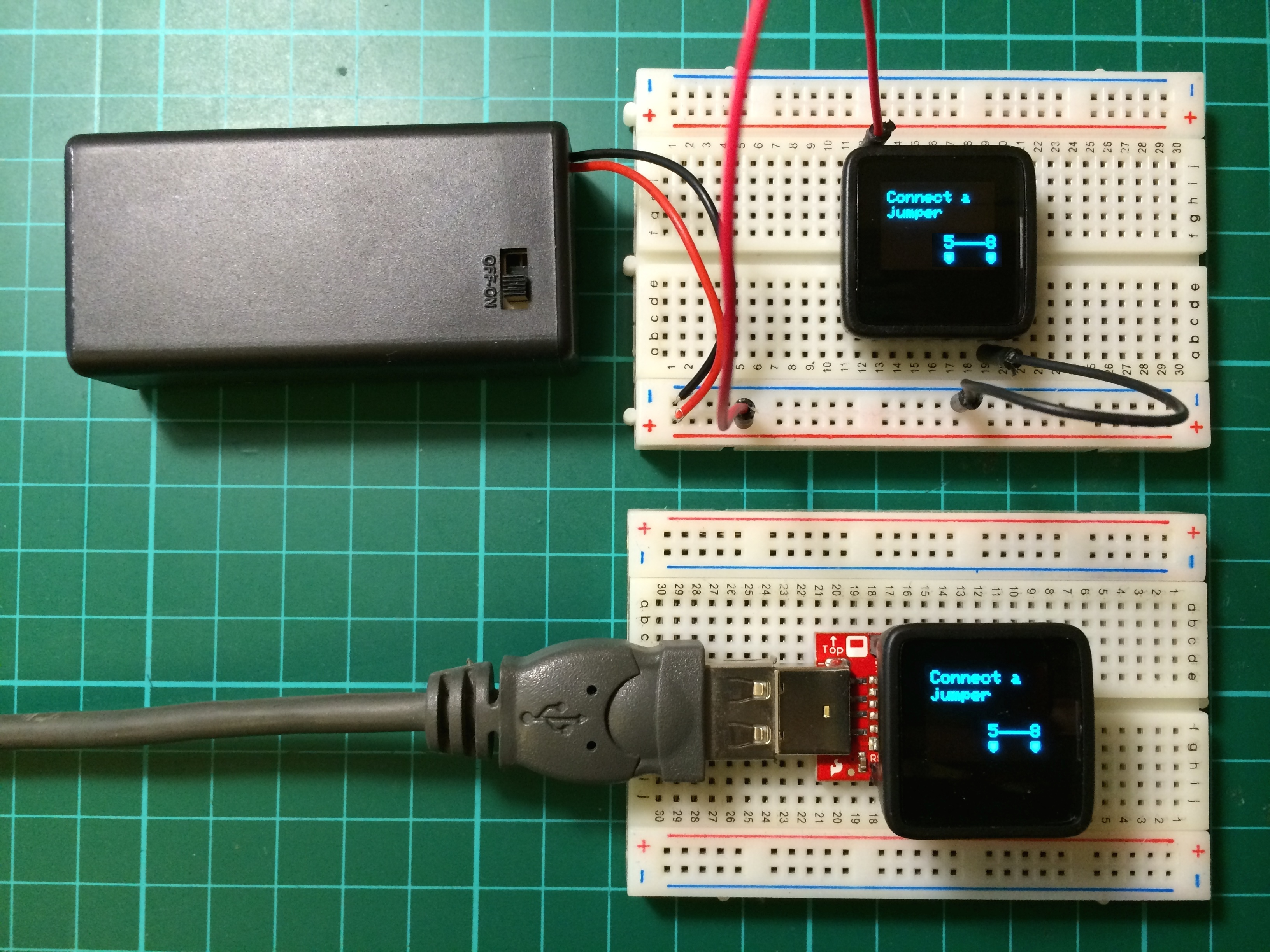 Two MicroView boards running the on-board tutorial. One board (top) powered from a 9V battery, the other (bottom) powered via the USB Programmer.