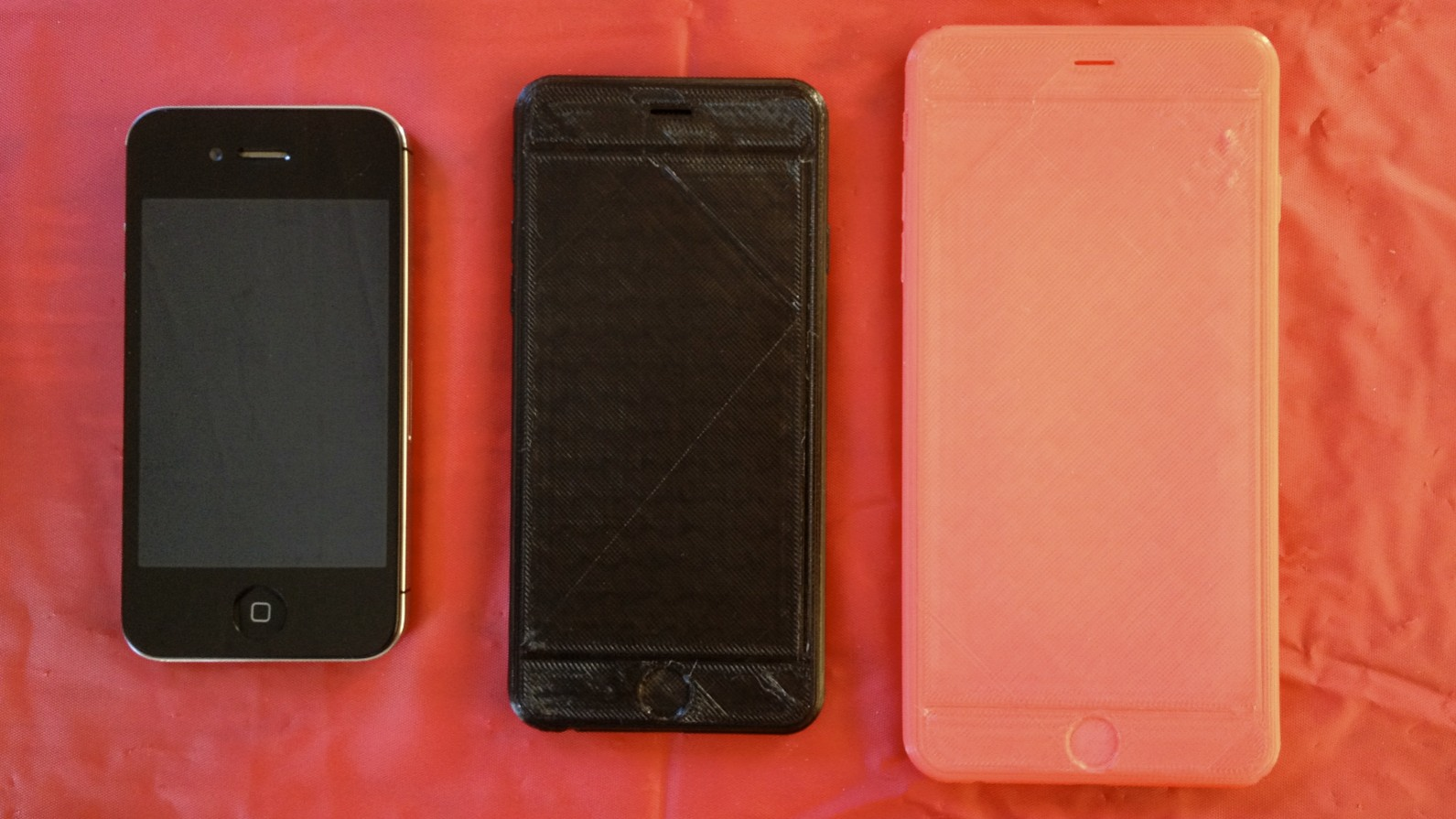 iPhone 4 compared to two prints of the 6 and 6 Plus.
